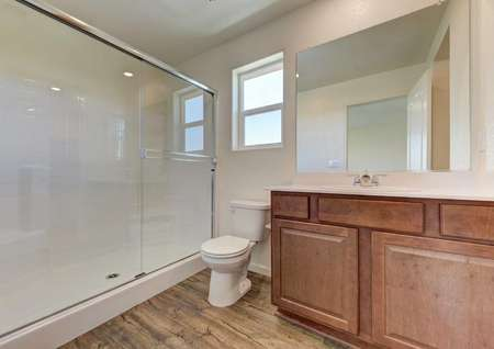 The bathroom in the Bonanza floor plan has a walk-in shower, quartz countertops, brown cabinets and wood-like floors.