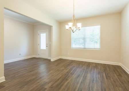 Jackson dining area with cream walls, wood flooring, and chandelier