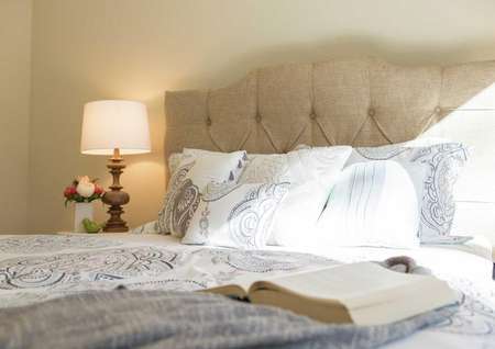Maple model home bedroom stage with a sandy color button tufted headboard, open book on top of a bluish comforter with white pillows on the bed, and a lit lamp with beige shade