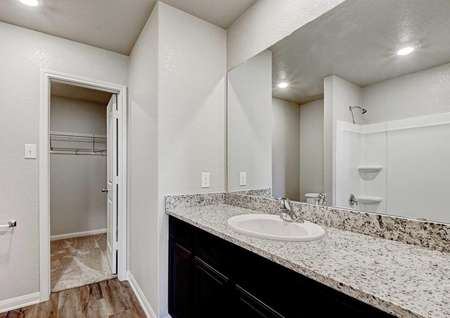 Carson master bathroom with extended granite countertop, brown cabinets, and access to walk in closet