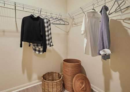 Closet with shelves that have clothes hanging from them.