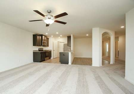 Spacious living room with carpet, ceiling fan, view of kitchen and dining room, hallway, recessed lighting and dark cabinets, natural light.