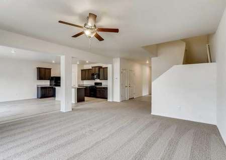 Harvard family room with ceiling fan, carpeted flooring, and stairs to second floor