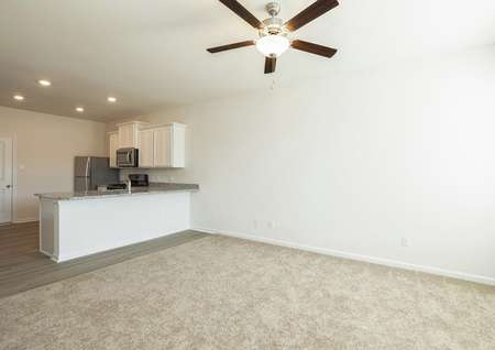 Living room with carpet and ceiling fan looks to breakfast bar and kitchen with white cabinets