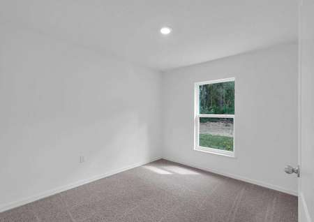 Secondary bedroom with recessed lighting and a window.