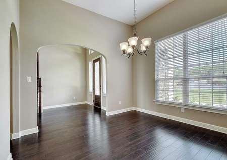 Timberline dining room with dark wood flooring, five-lamp chandelier, and white trimmed tan walls