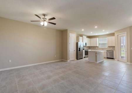 The Calabria floor plans living room that has tile flooring, a ceiling fan with lights, tan walls and white baseboards.