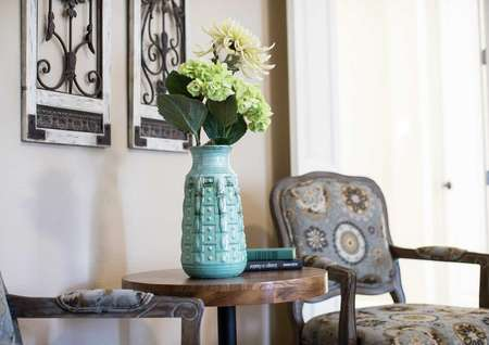 Sitting area with arm chairs and floral arrangement.