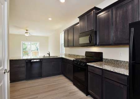 Columbia kitchen with custom brown cabinetry, recessed lights, and wood-style flooring