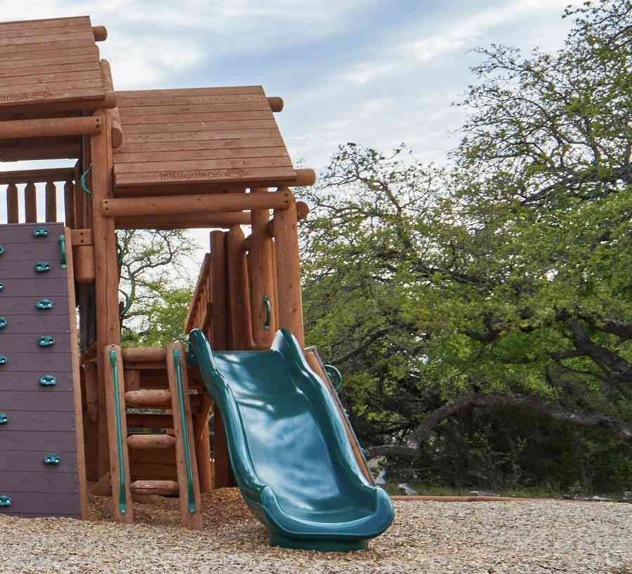 Rustic childrens playground with slides and climbing wall.