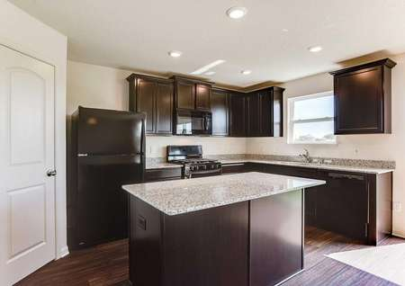 Nicollet kitchen with large food prep island, granite counterts, and brown cabinetry