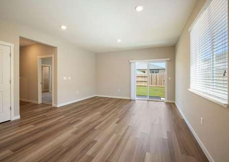 Incredible open family room with back yard access, wood style flooring and tan walls.