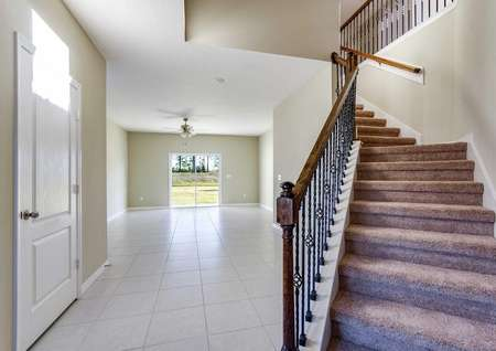 Living room with tile floors to the left and carpeted stairs that lead upstairs to the right in the Wekiva floor plan.
