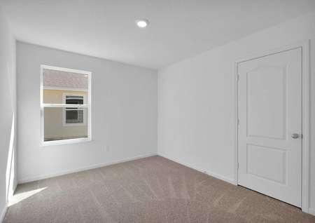A carpeted secondary bedroom with a large closet.
