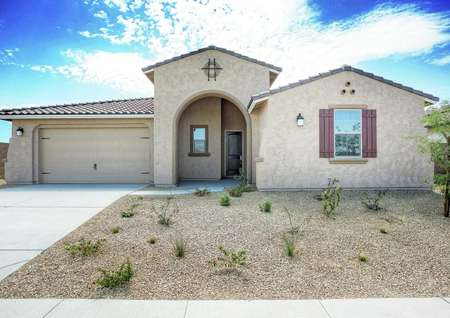 Bartlett finished house street view with desert landscaping, arched entryway, and beige stucco finish