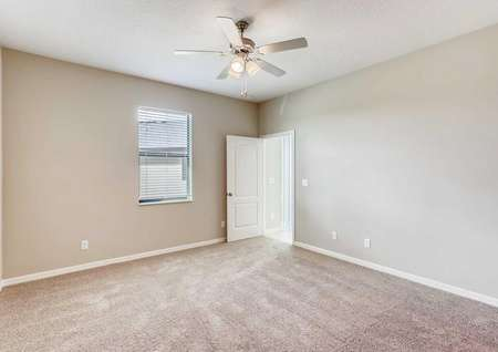 The Mateo model home's master bedroom. Tan walls, white baseboards, a ceiling fan and tan carpeting