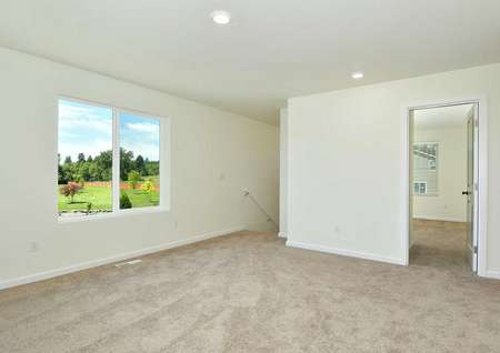 The Northwest Oak carpeted game room shown upstairs with a window showcasing a great view.