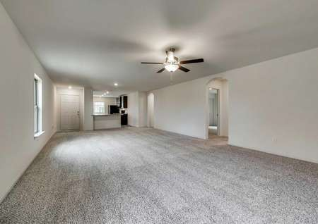 Santa Fe living room. Carpeted room that leads to hallways, kitchen and front door