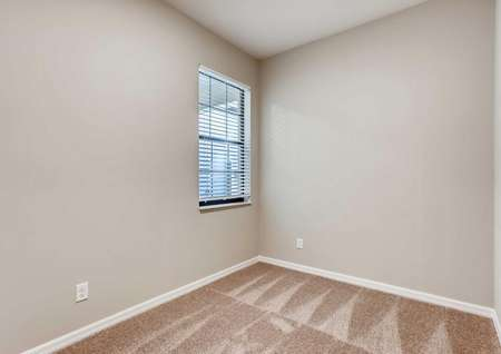 Secondary bedroom in the Mateo model home. Tan walls, baseboards and darker tan carpeting