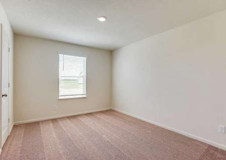 Chippewa bedroom with light carpets, white frame window and doors, and can lights