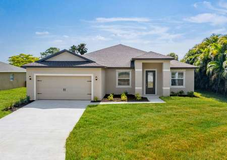 Stunning exterior of a one-story home with a beautiful front porch, long driveway and a two-car garage.