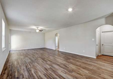 Jasper family room with brown wood tile floors, overhead lights and ceiling fan, and white on gray walls