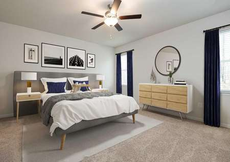 Staged master bedroom with king bed and dresser, modern decor in gray and navy, round mirror over dresser, ceiling fan and drapes on windows.