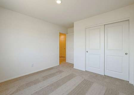 Secondary bedroom with tan carpet and closet with sliding doors.