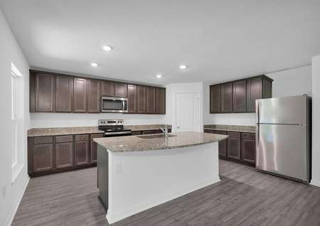 Kitchen island, upper-wood cabinets, recessed lighting and stainless steel appliances.