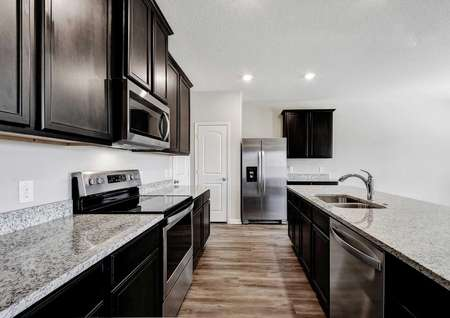 Shelby kitchen designed with gray granite countertops, stainless steel modern appliances, and wood-like ceramic flooring