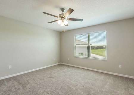 The master bedroom in the Sorrento floor plan with light brown carpet, white baseboards, tan walls and a ceiling fan.