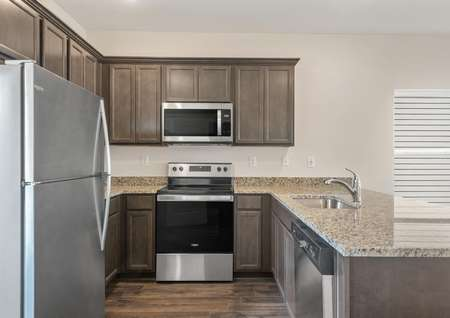 The kitchen has spacious granite countertops and stainless steel appliances.