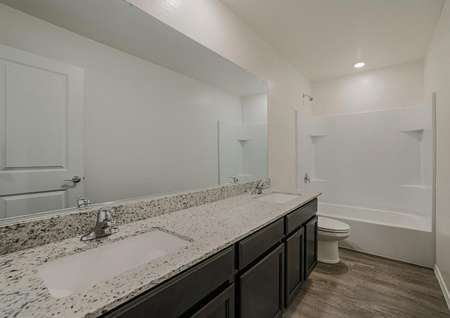 Gorgeous bathroom with dual sink vanity, granite countertops and a dual tub and shower.