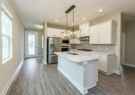 View of primary entrance leading to a chef-ready kitchen featuring quartz countertops and all new appliances.