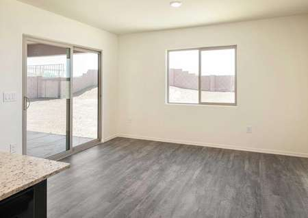The Roosevelt floor plan formal dining room with vinyl wood flooring and a view out the sliding glass door.