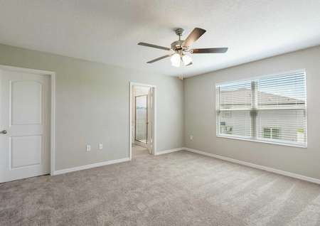 The master bedroom upstairs in the Calabria floor plan has light brown carpet, a large window and a door to the bathroom.