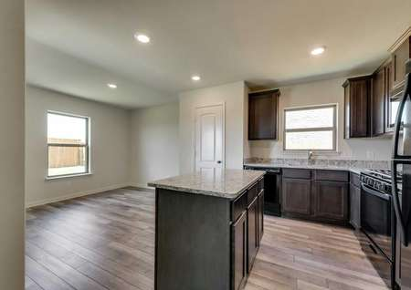 Sabine kitchen with dark brown cabinets, modern appliances, and wood finished floors