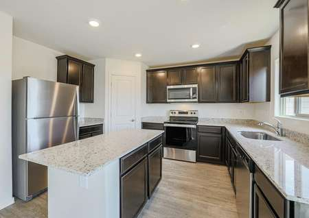 Modern kitchen with dark cabinets, beautiful granite countertops and stainless steel appliances.