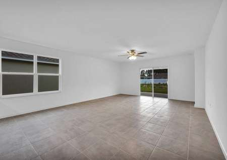 Large living room area in the St. Martin floor planthat has two windows, tile floors and a view outside through a sliding glass door.