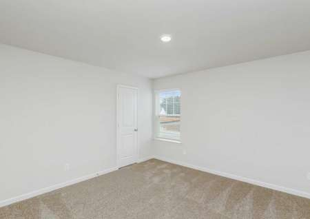 Spare bedroom with carpeted flooring and a window that lets in natural light.