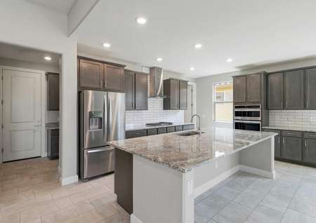 Hawley kitchen with stainless steel appliances, large granite island with eating bar, and brown wood cabinets