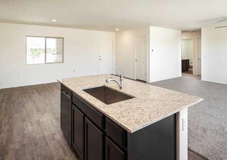 The Crescent floor plan kitchen shown with a granite kitchen island and a view of the living room.
