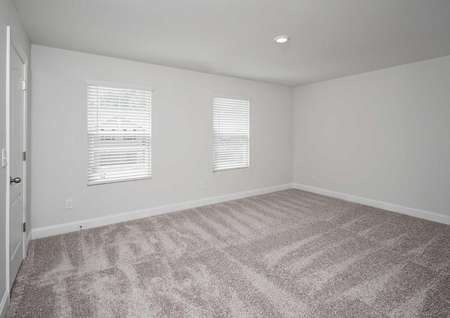 Spare bedroom with an overheadlight fixture, white walls andlight brown carpetin the Kiawah floor plan.