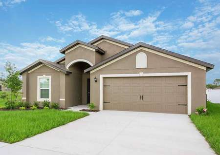 The exterior of the brown painted Estero floor plan with white trim around the windows and two-car garage.