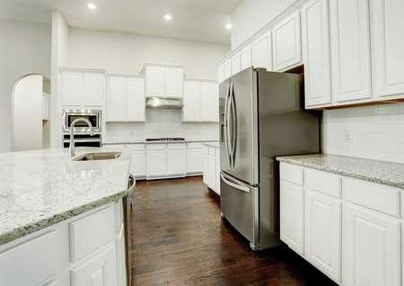 Bradley kitchen with white cabinetry, stainless steel appliances, and light color granite counters