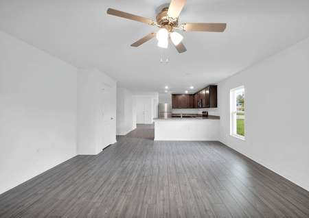 Elongated family room with a ceiling fan and a view of the chef-ready kitchen.