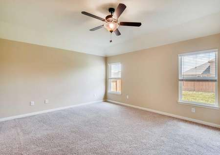 Spacious master bedroom with two windows, ceiling fan, two-tone paint and carpet in neutral palette.