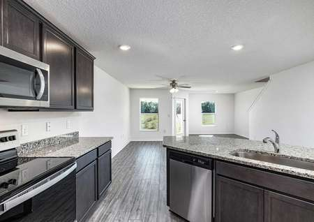 Open-concept kitchen space overlooking the home's family room and dining room.