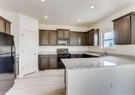 Yale kitchen with brown cabinets, granite counters, and modern appliances in black finish