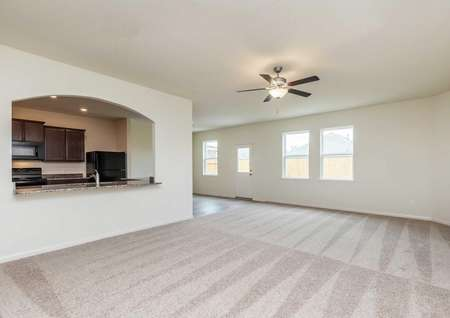 Osage floor plan, Living room with carpet, ceiling fan, kitchen with dark brown cabinets and granite countertops